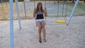 Junge gebräunte Frau, die auf einem Schwingen schwingt und ihre Füße baumelt stock footage