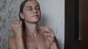 Junge gebräunte Frau nimmt eine Dusche mit nahen Augen stock video