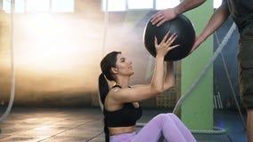 Junge geeignete Frau, die ABS mit Aerobicball mit attraktivem Sportmann trainieren l?sst stock video footage