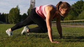 Junge-geeignete Frau, die auf grünem Gras im Park trainiert stock video