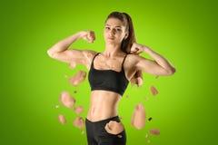 Junge geeignete Frauenstellungshalbe drehung und Ausführung der doppelten Bizepshaltung mit Stücken Fleisch in einer Luft um ihre stockfoto