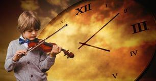 Junge gegen den grauen Hintergrund, der Violine und Stempeluhr spielt Lizenzfreie Stockbilder