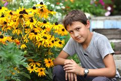 Junge gegen Sommerblume Lizenzfreies Stockbild