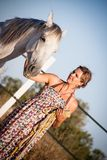 Junge gehende Frau eine Straße mit Pferd Lizenzfreie Stockfotos