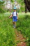 Junge geht durch den Wald stockbild