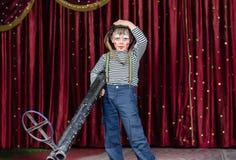 Junge gekleidet als Clown Holding Oversized Rifle Stockfotografie