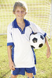 Junge gekleidet im Fußball Kit Standing By Goal Lizenzfreie Stockfotografie