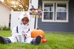 Junge gekleidet im Trick-oder Behandlungs-Raumfahrer-Kostüm auf Rasen Lizenzfreie Stockbilder