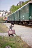 Junge, gekleidet im Weinlesemantel und im Hut, mit Koffer Stockfoto