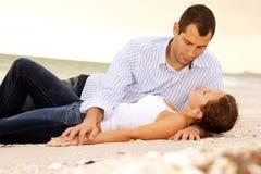 Junge Geliebte, die am Strand betrachtet einander legen Stockfotografie