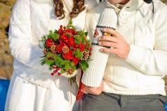 junge geliebte Paare, die im Winterpark sich wärmen Hände mit Schalen heißem Tee Stockfotos