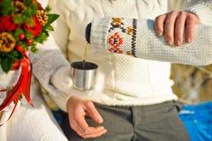 junge geliebte Paare, die im Winterpark sich wärmen Hände mit Schalen heißem Tee Lizenzfreie Stockfotos