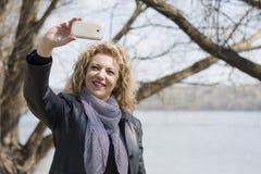 Junge gelockte blonde Frau, die Foto von macht Lizenzfreies Stockfoto