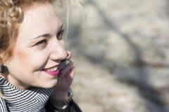 Junge gelockte blonde Frau, die herein am Telefon draußen spricht Stockfotografie