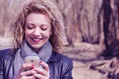 Junge gelockte blonde Frau, die am Telefon draußen eintippt Stockfotos