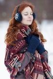 Junge gelockte rothaarige Frau in den blauen Handschuhen und in den Kopfhörern Lizenzfreie Stockbilder