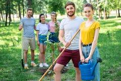 junge Gemeinschaft, die neue Bäume und das Freiwillig erbieten pflanzt stockbild