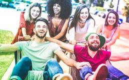 Junge gemischtrassige Freunde, die Spaß zusammen mit Einkaufswagen - tausendjährige Leute teilen Zeit mit Laufkatzen am Handelsma stockfoto