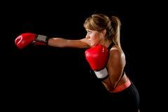 Junge gepasst und starkes attraktives Boxermädchen mit roten Boxhandschuhen werfendes aggressives Durchschlagstrainingstraining i Stockfoto
