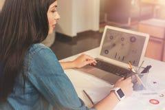 Junge Geschäftsdame, die an Laptop arbeitet und unten Informationen merkt Stockbilder