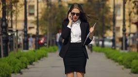 Junge Geschäftsdamenantworten bei einem Telefonanruf, lächelt und hält eine schwarze Datei in einem Park stock footage