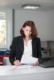 Junge Geschäftsfrau überprüft Vertrag Stockfoto