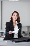 Junge Geschäftsfrau überreicht Vertrag Stockbilder