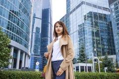 Junge Geschäftsfrau auf dem Hintergrund von Wolkenkratzern lizenzfreie stockfotos