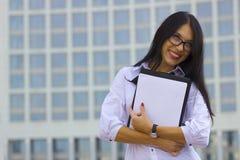 Junge Geschäftsfrau auf Hintergrund des Wolkenkratzers Lizenzfreie Stockfotos