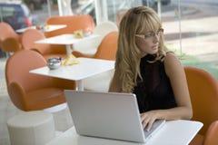Junge Geschäftsfrau auf Laptop am café Stockfotografie