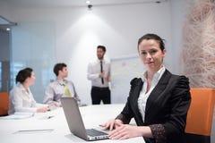 Junge Geschäftsfrau auf Sitzung unter Verwendung der Laptop-Computers Lizenzfreie Stockbilder