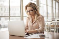 Junge Geschäftsfrau in den Brillen im sitzenden Arbeiten des Cafés an dem Laptop konzentriert Stockfoto