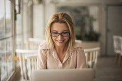 Junge Geschäftsfrau in den Brillen im sitzenden Arbeiten des Cafés an lächelnder netter Nahaufnahme des Laptops Lizenzfreie Stockfotos