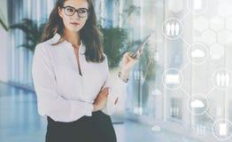 Junge Geschäftsfrau in den Gläsern hält einen Smartphone Im Vordergrund sind virtuelle Ikonen von Wolken, digitale Geräte Lizenzfreies Stockbild