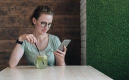 Junge Geschäftsfrau in den Gläsern sitzt in einem Café bei Tisch, trinkt ein Getränk und benutzt einen Smartphone Mädchenfunktion Stockbild