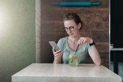Junge Geschäftsfrau in den Gläsern sitzt in einem Café bei Tisch, trinkt Getränk und benutzt Smartphone Lizenzfreie Stockbilder
