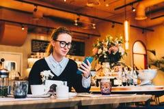 Junge Geschäftsfrau in den Gläsern sitzt im Café bei Tisch, benutzt Smartphone Auf Tabelle ist Tasse Kaffee Mädchenfunktion Stockfotografie