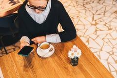 Junge Geschäftsfrau in den Gläsern sitzt im Café bei Tisch, benutzt den Smartphone und trinkt Kaffee Mädchenfunktion Lizenzfreie Stockfotos