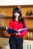 Junge Geschäftsfrau in der roten Bluse mit einem Ordner von Dokumenten Lizenzfreie Stockfotografie