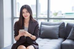 junge Geschäftsfrau des schönen überzeugten Asiaten, die den Smartphone stationiert auf Sofa, auf Fenster im Lobbystadthintergrun lizenzfreie stockfotos