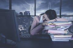 Junge Geschäftsfrau, die über Dokumenten schläft Stockbild
