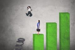 Junge Geschäftsfrau, die über ihren Rivalen springt stockbild