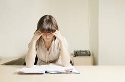 Junge Geschäftsfrau, die über Papieren denkt Lizenzfreies Stockbild