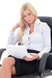Junge Geschäftsfrau, die auf Bürostuhl sitzt und mit La arbeitet Lizenzfreies Stockbild