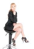 Junge Geschäftsfrau, die auf einem Barhocker über weißem Hintergrund aufwirft Stockbild