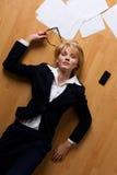 Junge Geschäftsfrau, die auf Fußboden liegt Stockfotos
