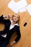 Junge Geschäftsfrau, die auf Fußboden liegt Stockbilder