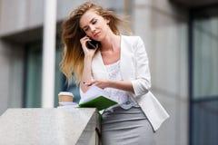 Junge Geschäftsfrau, die auf Mobiltelefon beim Gehen im Freien spricht Lizenzfreie Stockfotos