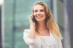 Junge Geschäftsfrau, die auf Mobiltelefon beim Gehen im Freien spricht Stockbilder