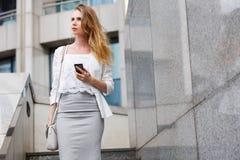 Junge Geschäftsfrau, die auf Mobiltelefon beim Gehen im Freien spricht Lizenzfreies Stockfoto